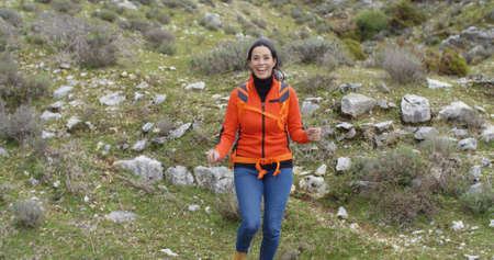 striding: Vivacious attractive young woman in a colorful orange jacket enjoying a mountain hike striding towards the camera with a smile  wide angle and copy space Stock Photo
