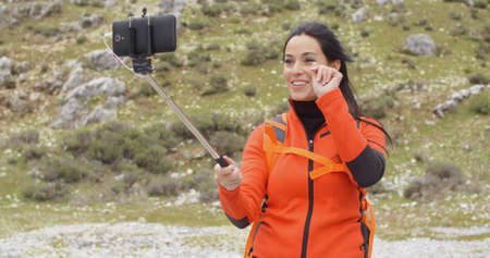 memento: Smiling young backpacker using a selfie stick to take her photograph on a smart phone as a memento of her hike in the mountains Stock Photo