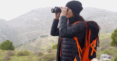 산에서 안개가 자욱한 하이킹을 즐기고 행복 웃는여자가 배낭을 들고 추운 날씨에 대해 따뜻하게 감쌌다.