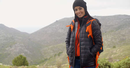 warmly: Happy smiling woman enjoying a misty hike in the mountains wrapped up warmly against the cold weather carrying a backpack