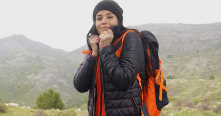 snuggling: Young active woman hiking on a mountainside with her backpack in winter snuggling into her warm anorak with a smile against a cold landscape