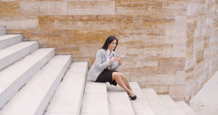executive woman: Side view of happy young business woman in gray blazer and skirt sitting alone on marble staircase using her phone