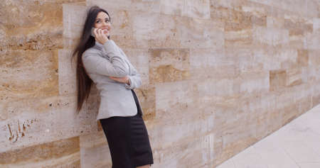 marble wall: Carefree smiling business woman leaning against large marble wall looking up and talking on phone Stock Photo