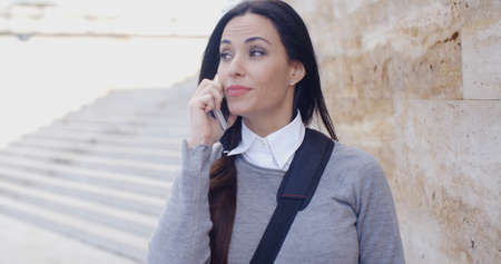 large woman: Astonished young woman in gray sweater and ponytail looking out while talking on phone and leaning against large marble wall with staircase in background outdoors