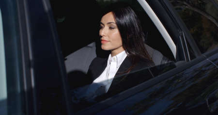Beautiful young female executive with button collar sitting in rear seat of limousine with confident expression Stock Photo