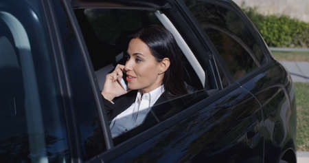 Serious young female executive with button collar on phone and sitting in rear seat of limousine with window down Stock Photo