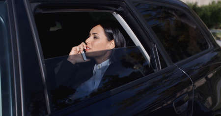 tinted: Serious young female executive with button collar on phone and sitting in rear seat of limousine with window down Stock Photo