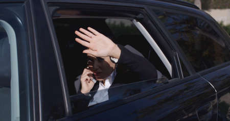 Annoyed female business woman on phone in back of car with window down trying to block the view with hand near face