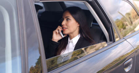Beautiful young business woman with long hair in conversation on phone while sitting in rear seat of limousine with window down