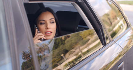 beautiful black woman: Beautiful young business woman in conversation on phone while sitting in rear seat of limousine looking out from window Stock Photo