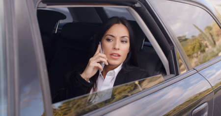 business woman phone: Serious young woman in business attire on cell phone while sitting in rear seat of limousine looking outside from open window Stock Photo