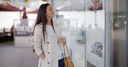 exclusive: Stylish young woman browsing in a shopping mall looking at merchandise for sale in the store windows