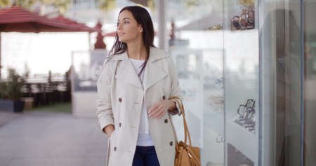 window shopper: Smiling stylish woman walking past a shop window with a smile as she walks down an urban street towards the camera Stock Photo