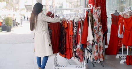 window shopper: Young woman looking for a colorful red dress searching through garments hanging on a rail outside a shop in an urban street