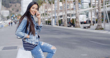 mezclilla: mujer joven atractivo de moda en un traje de mezclilla que se encarama en una pared en una paseo urbano que habla en su móvil y sonriendo a la cámara