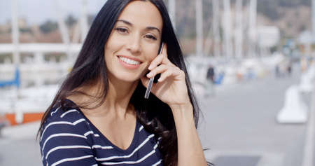 yacht people: Attractive smiling woman using a mobile phone outdoors on an urban promenade  close up head and shoulders view