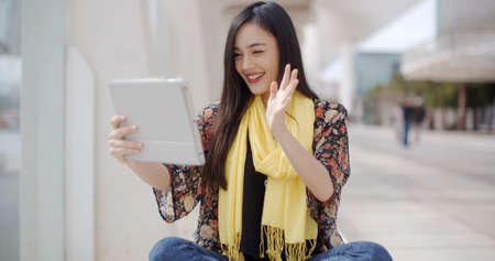 asian lady: Smiling beautiful Asian woman wearing yellow scarf waving hand at tablet computer that she is holding