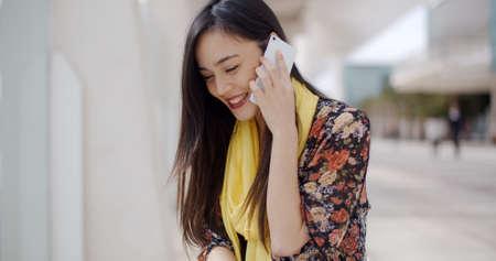hablando por telefono: Mujer joven atractiva elegante de escuchar una llamada en su teléfono móvil con una sonrisa de placer en un entorno urbano