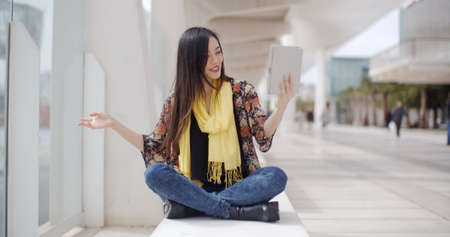 Smiling beautiful Asian woman wearing yellow scarf waving hand at tablet computer that she is holding