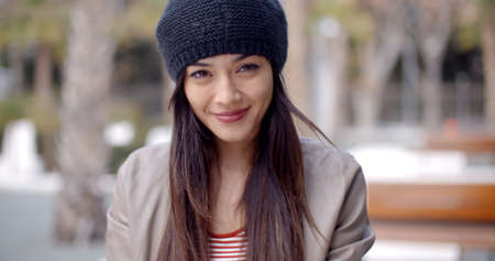 asian adult: Pretty thoughtful young woman with long brown hair in a woolly cap looking at the camera with a gentle smile  head and shoulders portrait Stock Photo