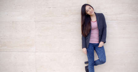 lean back: Trendy young woman posing against a textured off white wall with one foot raised smiling at the camera  with copy space