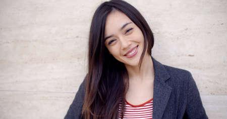 Mujer joven magnífica con el pelo largo morena y una sonrisa vivaz mirando a la cabeza de la cámara y los hombros contra una pared de la textura con copia espacio Foto de archivo