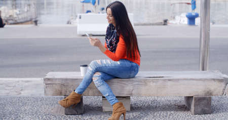 woman on phone: Relaxed confident young woman sitting on a bench on an urban promenade chatting on a mobile phone with a smile  close up wide angle