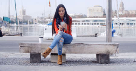 hablando por telefono: Young woman sitting on a bench in town checking her mobile phone for text messages with a smile  wide angle and copy space Foto de archivo
