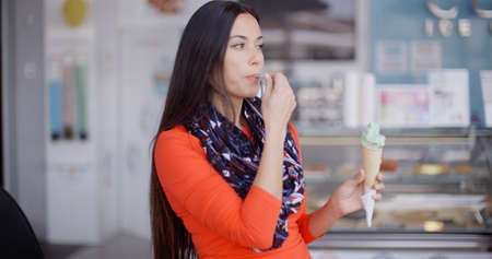 Smiling young woman savoring a tasty ice cream cone as a summer treat indoors in a cafeteria or ice cream parlor