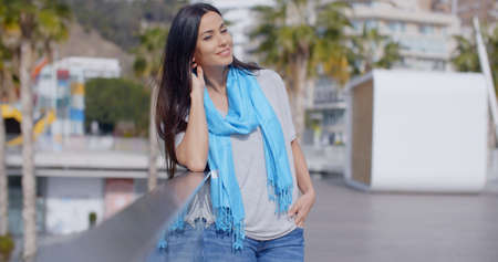 leans on hand: Gorgeous young grinning woman in long black hair and blue scarf with hand in hair as she leans on glass railing overlooking park