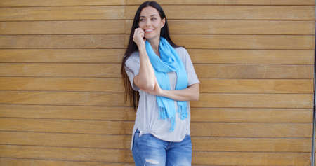 adult wall: Attractive young adult female in blue scarf and torn jeans talking on cell phone and adjusting hair while leaning against wood paneled wall