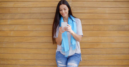 adult wall: Smiling young adult female in blue scarf and torn jeans texting on cell phone while leaning against wood paneled wall Stock Photo