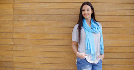 adult wall: Smiling young adult female in blue scarf and jeans with both hands in pockets while leaning against wood paneled wall