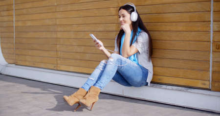Attractive young woman listening to her music on stereo headphones as she sits on the ground in front of a closed kiosk Stock Photo