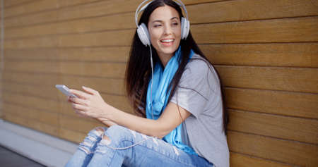 Attractive young woman listening to her music on stereo headphones as she sits on the ground in front of a closed kiosk