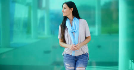 blue green background: Gorgeous happy woman in long black hair with smile looking sideways in front of blurry building reflected in green glass