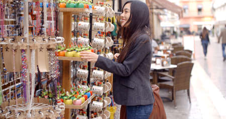 Happy relaxed young woman checking out shop merchandise on an outdoor rack in a pedestrian mall with a smile  three-quarter side view