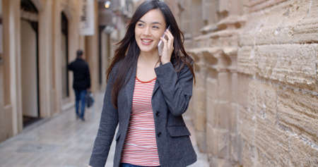 alley: Young woman walking through town with her mobile phone listening to a call with a smile as she strides along a narrow alley