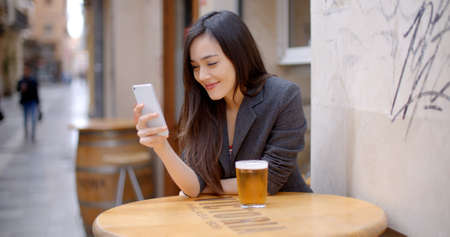 handphone: Smiling young woman relaxing with a beer at an open-air table in town with her mobile phone in her hand as she reads a text message.