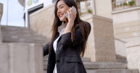 business lifestyle: Low angle view of a happy young woman standing on a flight of stairs in town chatting on her mobile with a beaming smile Stock Photo