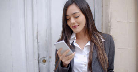 mobile business: Attractive young woman sending a text message on her mobile phone as she stands in the entrance to a building leaning against the side of the door.