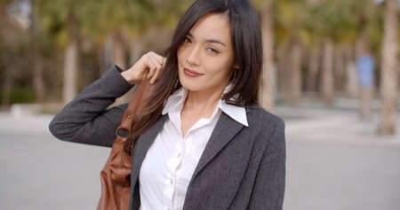 woman business suit: Gorgeous single adult Asian business woman with long hair smiling as she puts purse strap over her shoulder Stock Photo