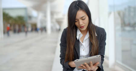 asian businesswoman: Stylish young woman using her tablet computer to browse the internet as she relaxes on a bench on an urban promenade Stock Photo