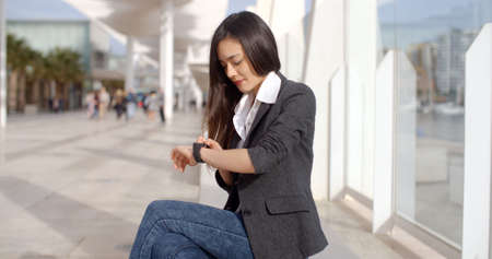 rendezvous: Attractive woman checking the time on her wristwatch as she sits on a bench in town waiting for a rendezvous