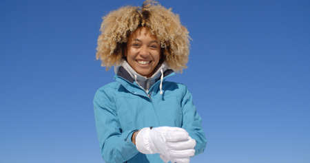frizzy hair: Cute young single woman in frizzy hair and winter coat with thick white ski gloves under clear blue sky