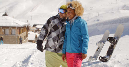 snow break: Beautiful young woman in blond curly hair leaning on friend taking a break from snowboarding at ski resort surrounded by thick white snow outside