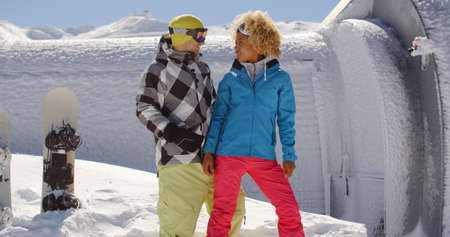 snow break: Adult young woman in blond curly hair looking at happy friend with goggles taking a break from snowboarding at ski resort surrounded by thick white snow outside
