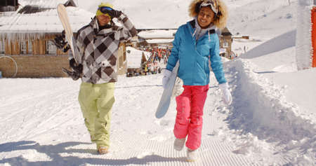 ski walking: Young couple walking in heavy winter snow in a mountain ski resort carrying their snowboards Stock Photo