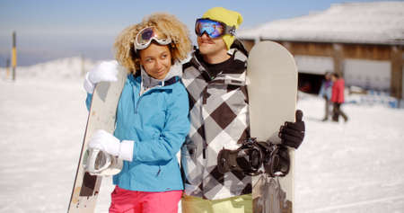 lovingly: Affectionate young couple posing arm in arm with snowboards smiling lovingly into each others eyes  close up upper body