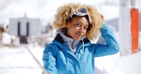 afro hairdo: Attractive young woman with a modern afro hairdo posing in winter snow at a ski resort with her hand to her head as she smiles at the camera  she holding a selfie stic with smart phone attached  close up view